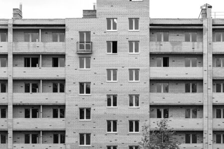 Multistorey new large apartment built of reinforced concrete. Under some Windows there is a platform for air conditioners.
