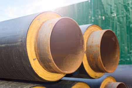 The long metal pipeline is rusty and insulated. Black plastic insulation. The background is blurred.