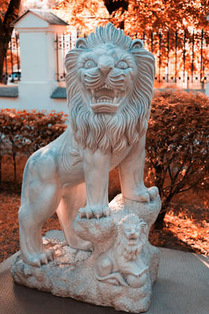 White marble lion statue against the background of trees in the Park. Small details of the sculpture are visible.