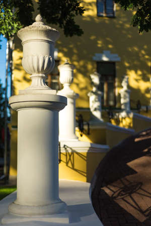 Porch with white concrete columns. Shallow depth of field. The background is blurred. The house is in the background.