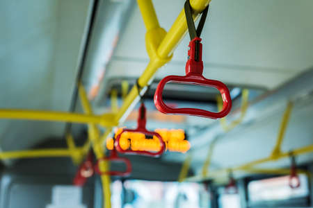 Handles on public transport during the day. There is no one in transport. The background is blurred.