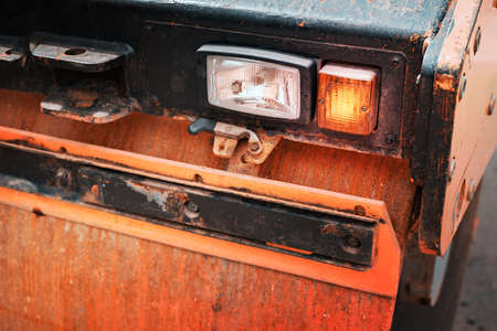 Old rusty asphalt rolling machine with broken lights. The background is blurred. 免版税图像