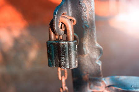 A rusty chain with a lock on an iron wrought-iron gate. The background is very blurry. 免版税图像
