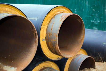 The long metal pipeline is rusty and insulated. Black plastic insulation. The background is blurred. 免版税图像