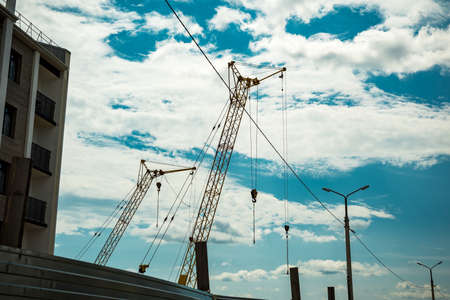 Several construction cranes of yellow color under summer cloudy sky.