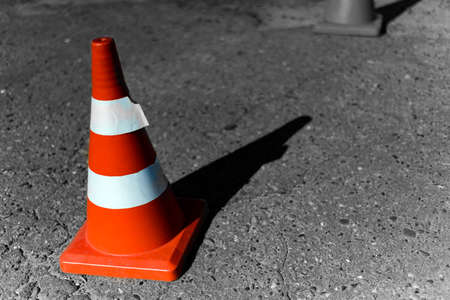 Traffic signal cone with white rings on old cracked asphalt. The background is blurred.