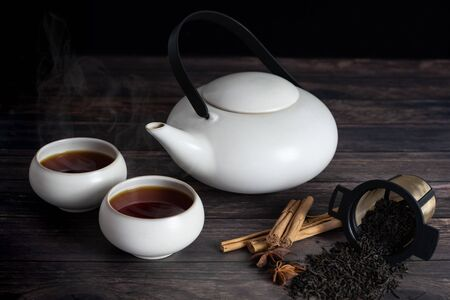 two cup of tea, teapot, cinnamon stick, tea strands, strainer, star anise on wooden table.