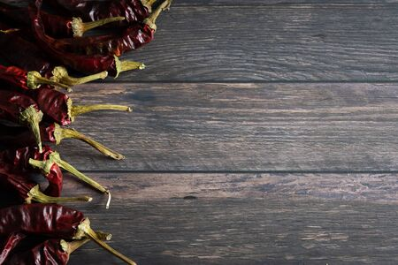 Wooden background with group of dried chilli peppers on the side