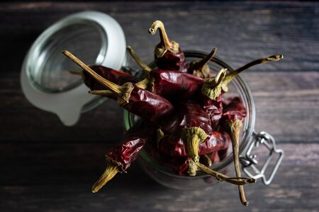 Top view of glass jar with group of dried chilli peppers on wooden table Reklamní fotografie