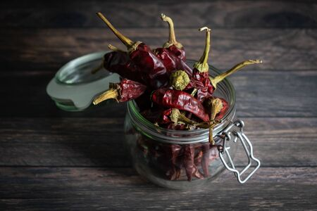 Glass jar with group of dried chilli peppers on wooden table