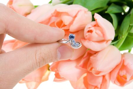 Hand with a ring on a background of flowers Stock Photo - 2379349