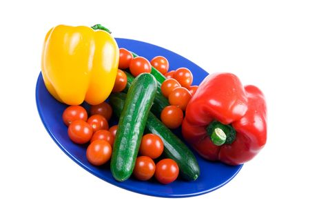 Set of vegetables on a dark blue plate isolated on a white background photo