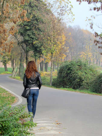Lonely woman strolling down the street along a tree lined avenue in autumn
