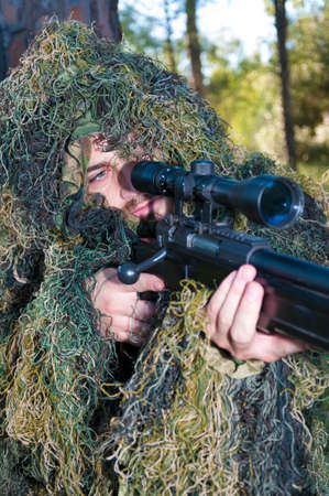 Sniper soldier in combat position with camouflage clothing in field Stock Photo