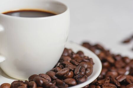 A cup of coffee on old wooden table with some beans a spoon. Stok Fotoğraf