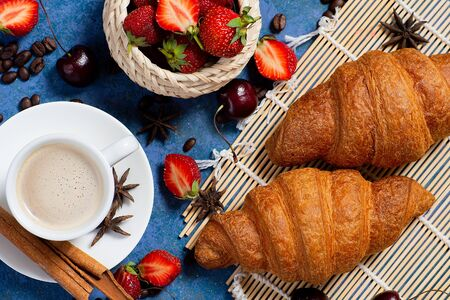 Croissant with fresh berries and coffee cup at blue table top view. Foto de archivo - 135494757