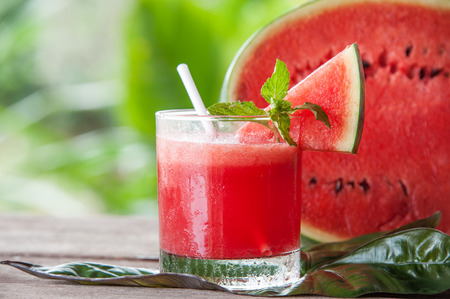 Watermelon smoothie in a glass placed on a wooden floor.