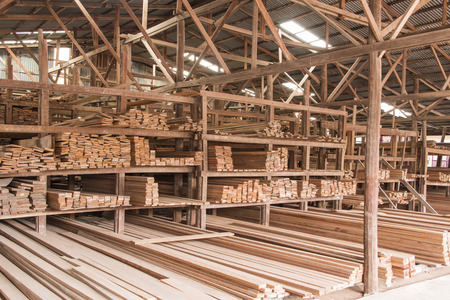 Wood stacked on shelving inside a lumber yard Stock Photo
