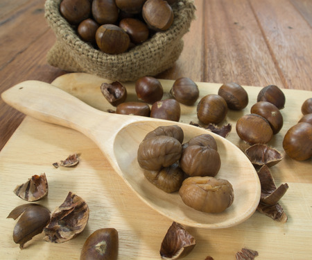 Chestnuts, peeled and seeded in the wooden spoon photo