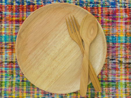 wooden dish , wooden spoon and wooden fork on fabric background