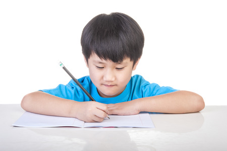 child studying: Little boy writing white paper on the table Stock Photo