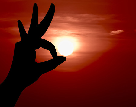 Ok hand sign silhouette. On sunset background.