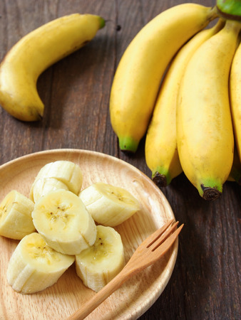 banana slice: Banana slice on a plate placed on a wooden table. Stock Photo