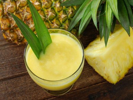 pineapple juice and pineapple on wood table. for health