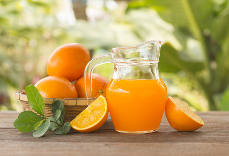 Orange juice is placed on a wooden table with natural light.