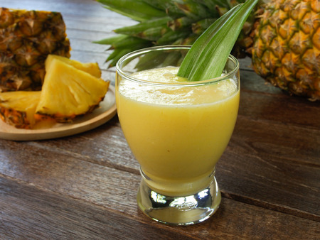 pineapple: pineapple juice and pineapple on wood table. for health