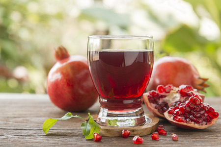 glass of pomegranate juice with fresh fruits on wooden table.