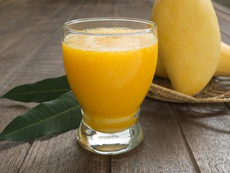 mango: Sok z mango i mango na stole drewna