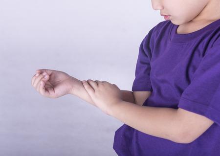 Jungen überprüft seinen Arm mit Muskelschmerzen. Standard-Bild - 40549506