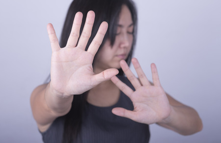 to restrain: woman showing her denial with NO on her hand