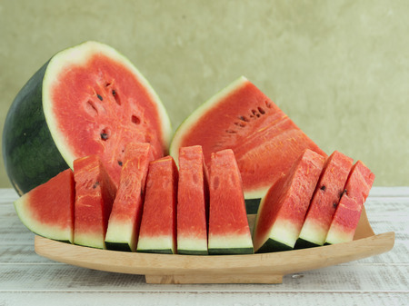 watermelon slice: watermelons and watermelon pieces  placed in wooden plates.