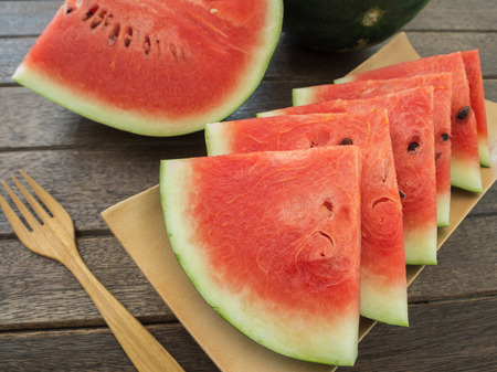 watermelons and watermelon pieces  placed in wooden plates.