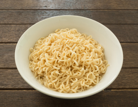 cooked instant noodle: Instant noodles in bowls on wood table Stock Photo