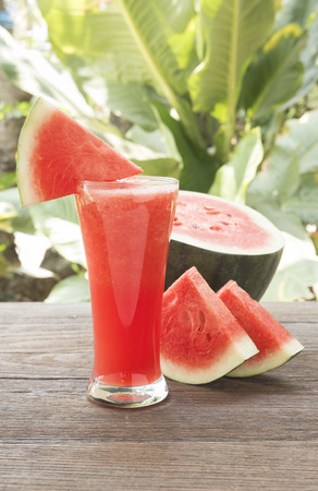 watermelon juice: watermelon juice and sliced ripe watermelon on wooden table. Stock Photo