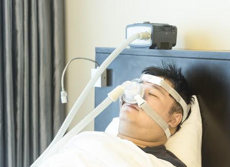 apnoe: Mann mit Schlaf Apnoe und CPAP-Maschine