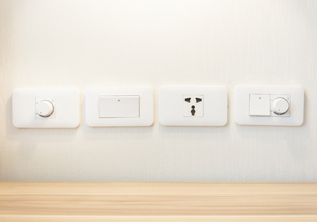 switches: Electronic light switches and plug sockets mounted on the wall.
