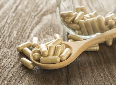 oleifera: Hierbas c�psula (Moringa oleifera) en la cuchara de madera.