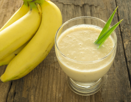 banana slice: Banana smoothie in a glass is placed on a wooden table.