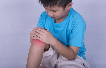 dolor muscular: dolor en la rodilla, la celebración de niño dolorido y muscular doloroso, rodilla llena de color rojo brillante lugar. Persona lesionada en el ejercicio o jugando. Foto de archivo