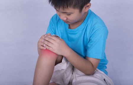 knee pain, child holding sore and painful muscle, knee filled with red bright place. Person injured when exercising or playing. Stock Photo