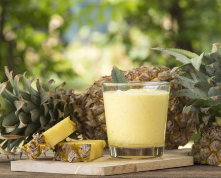 tropical fruits: Pineapple juice and pineapple slice placed on a wooden table.