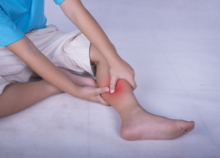 Calf leg pain, child holding sore and painful muscle, sprain or cramp ache filled with red bright place. Person injured when exercising or playing.