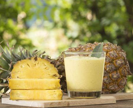 パイナップル ジュースやパイナップルのスライスは、木製のテーブルに配置されます。