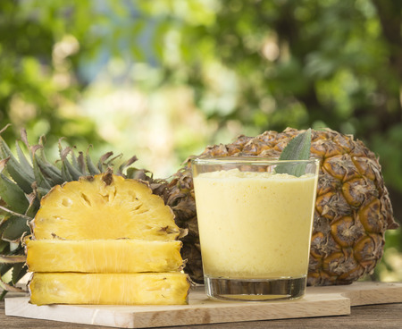 and pineapple juice: Pineapple juice and pineapple slice placed on a wooden table.