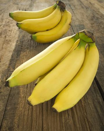 banane: Bouquet de bananes m�res plac� sur une table en bois.