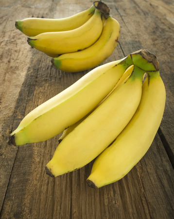 Bunch of bananas ripe placed on a wooden table.
